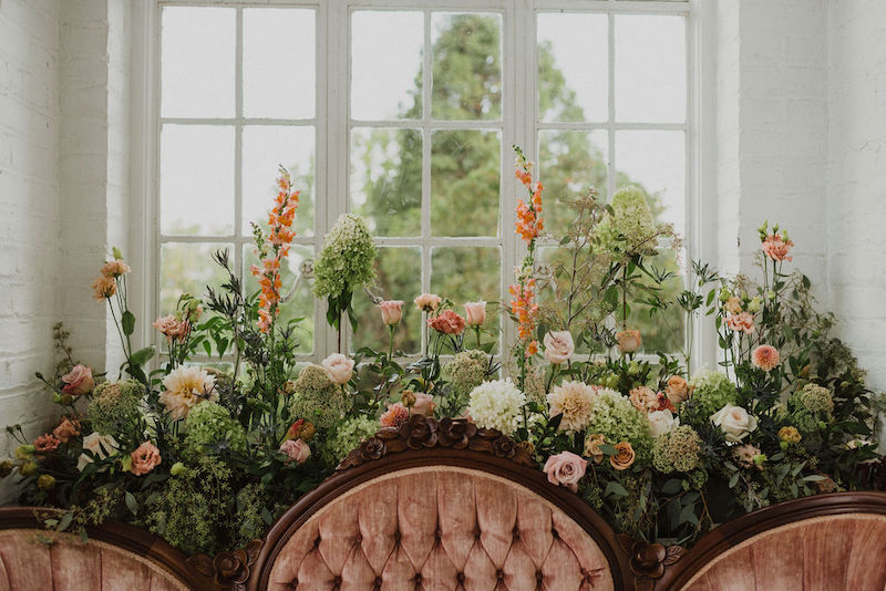vintage velvet love seat surrounded by natural flowers at The Historic Bleakhouse Venue photographed by Finding Eden Photography || Melissa Timm Designs www.melissatimmdesigns.com